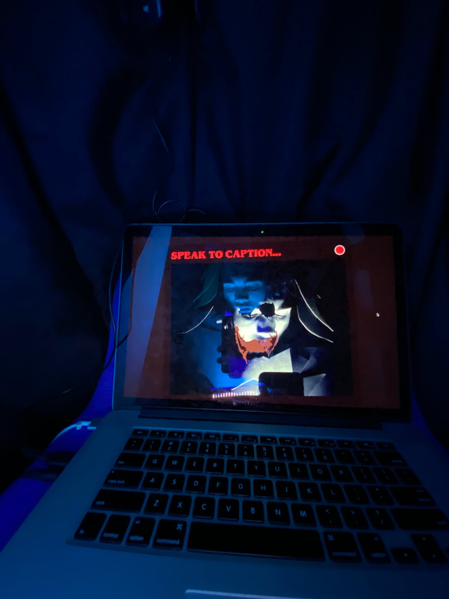MacBook Pro bathed in blue light with project onscreen