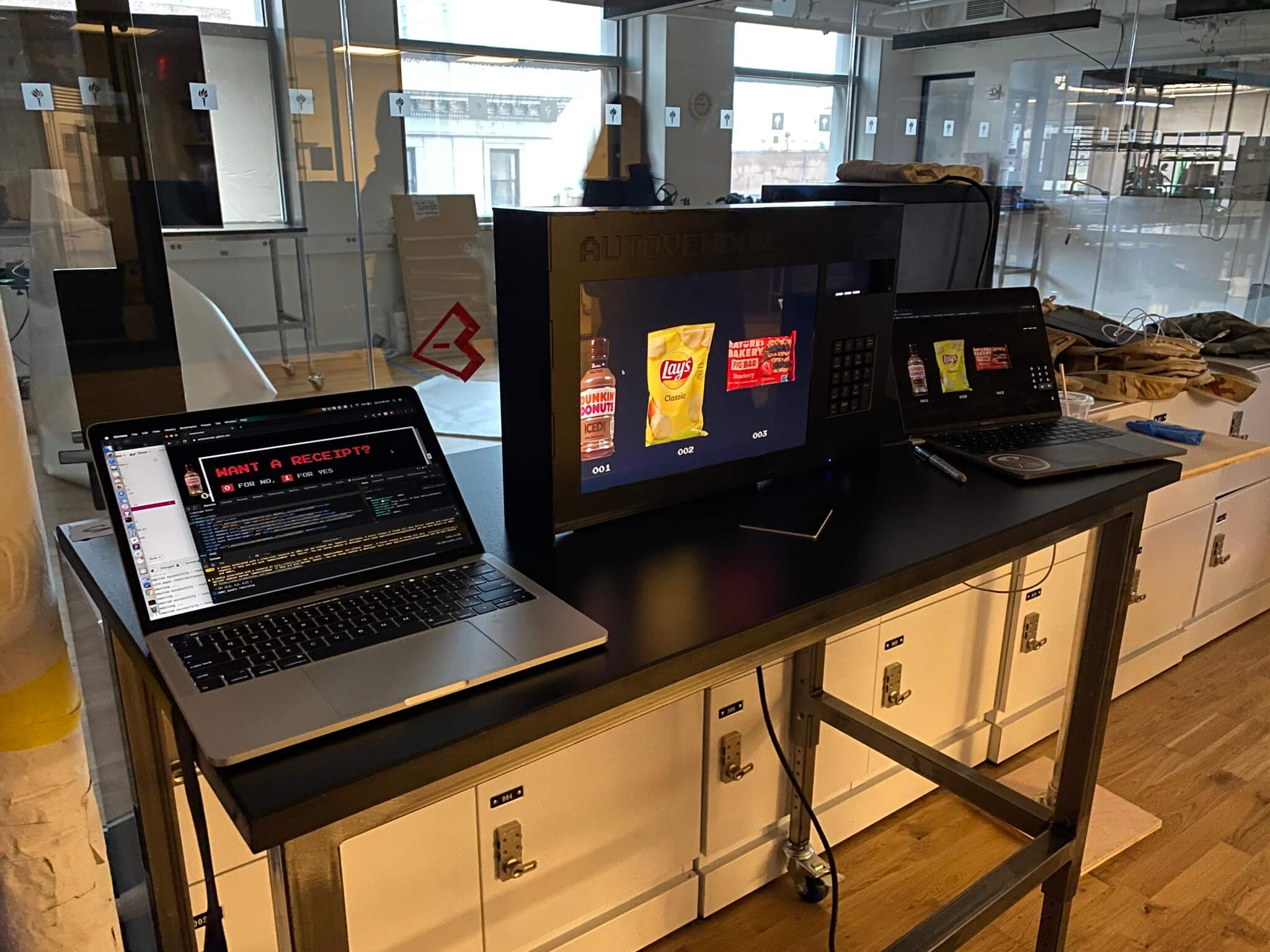 Setting up the installation, with two laptops surrounding the vending machine
